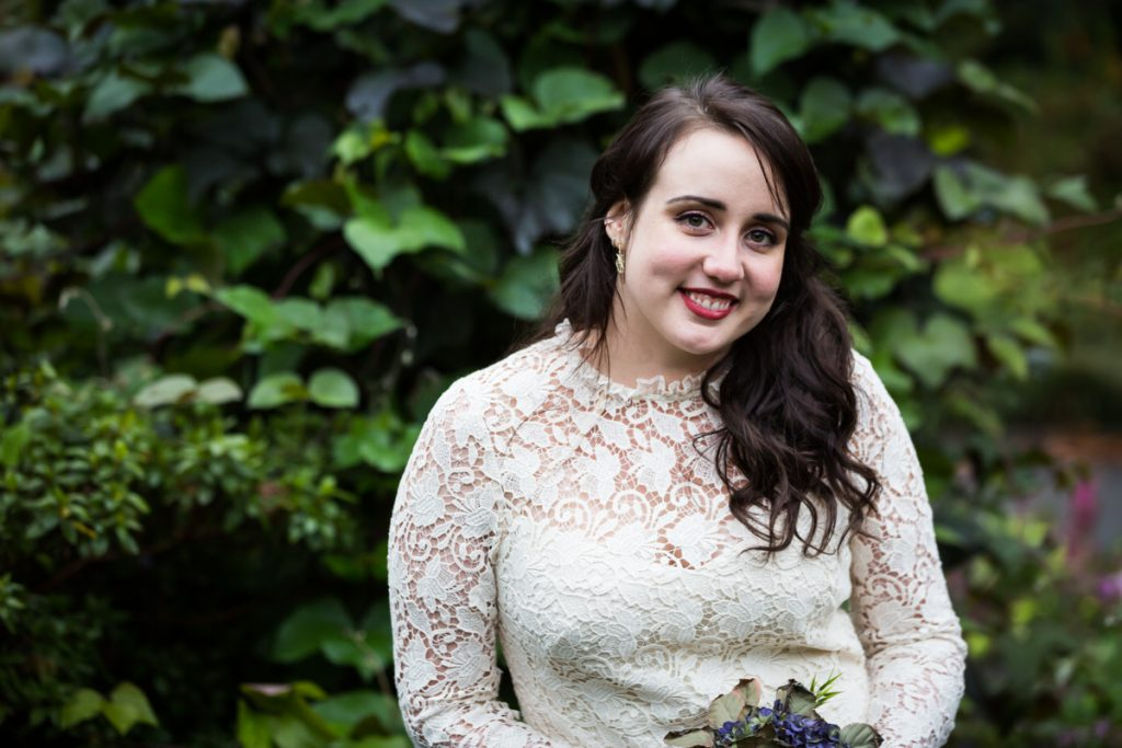 Portrait of bride in front of green bush in Fort Tryon Park