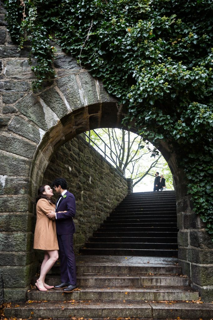 Couple kissing under stone archway in Fort Tryon Park
