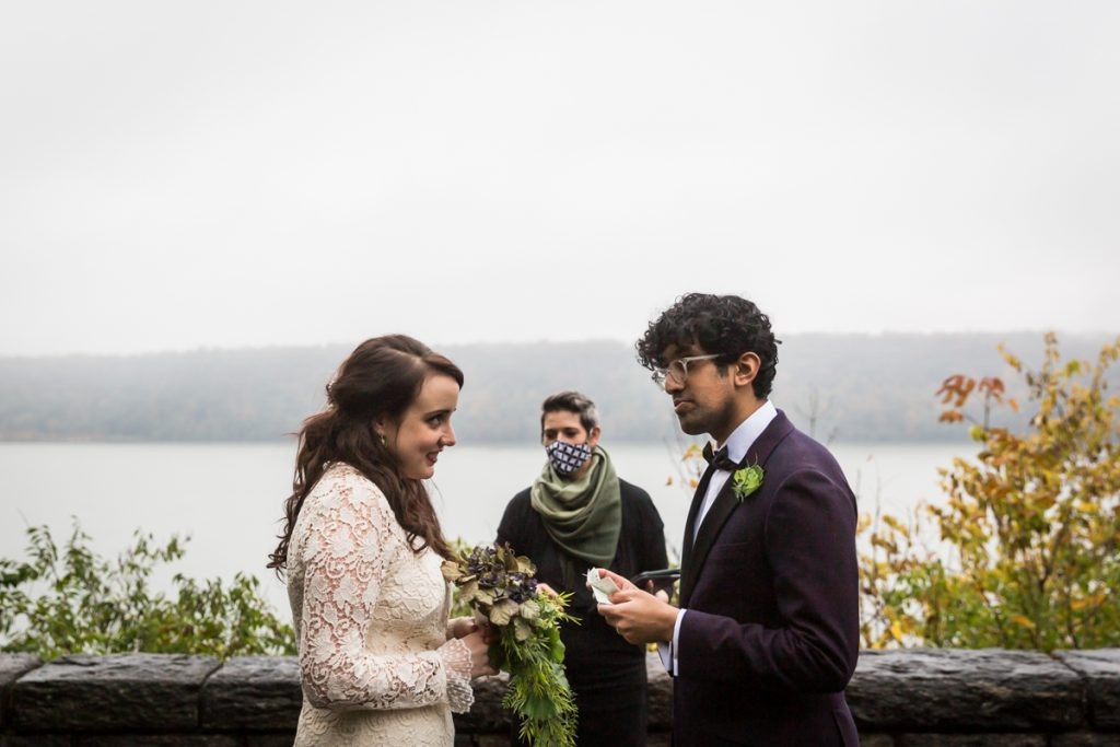 Couple swapping vows with view of Hudson River for an article on how to get married in Fort Tryon Park