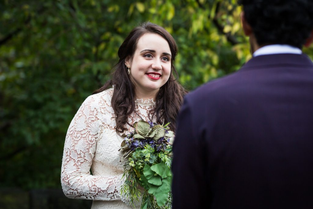 Bride listening to groom say vows in Fort Tryon Park