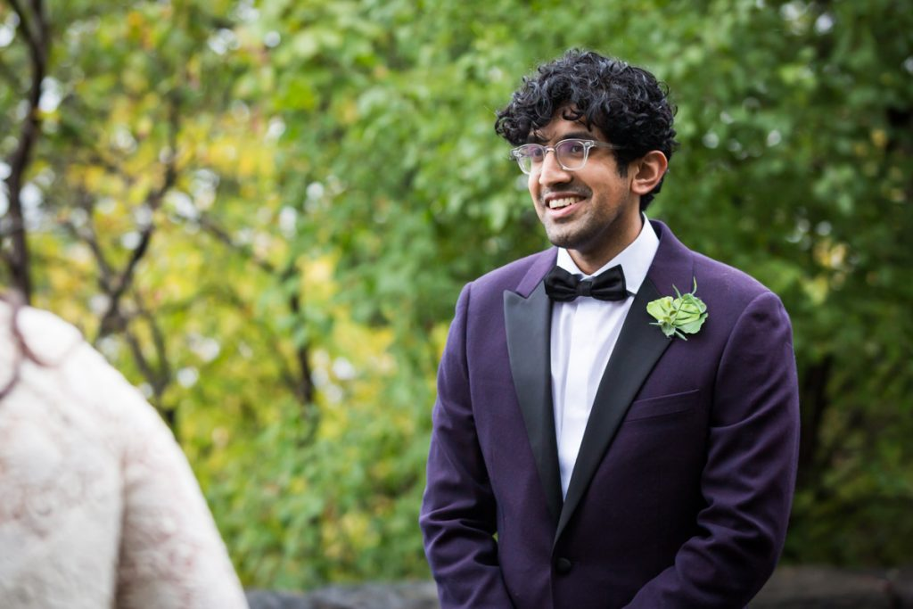 Groom listening to bride say vows in Fort Tryon Park wedding