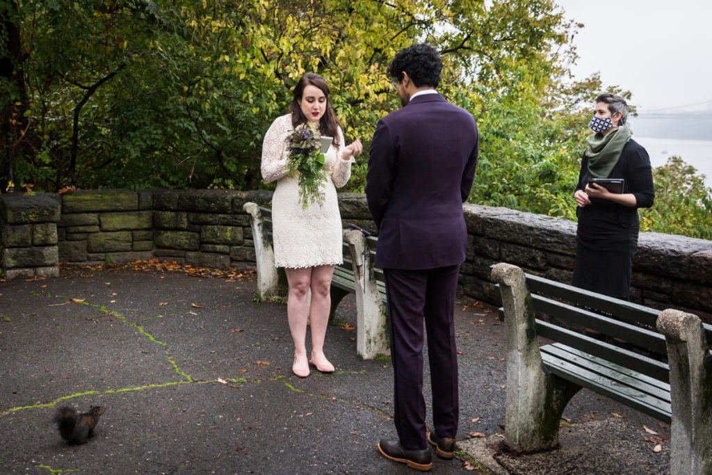 Couple exchanging vows in Fort Tryon Park with squirrel watching