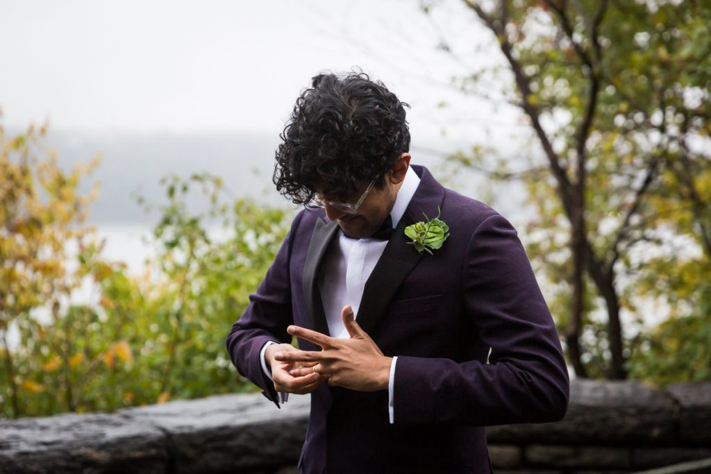 Groom struggling to put on wedding ring during Fort Tryon Park wedding