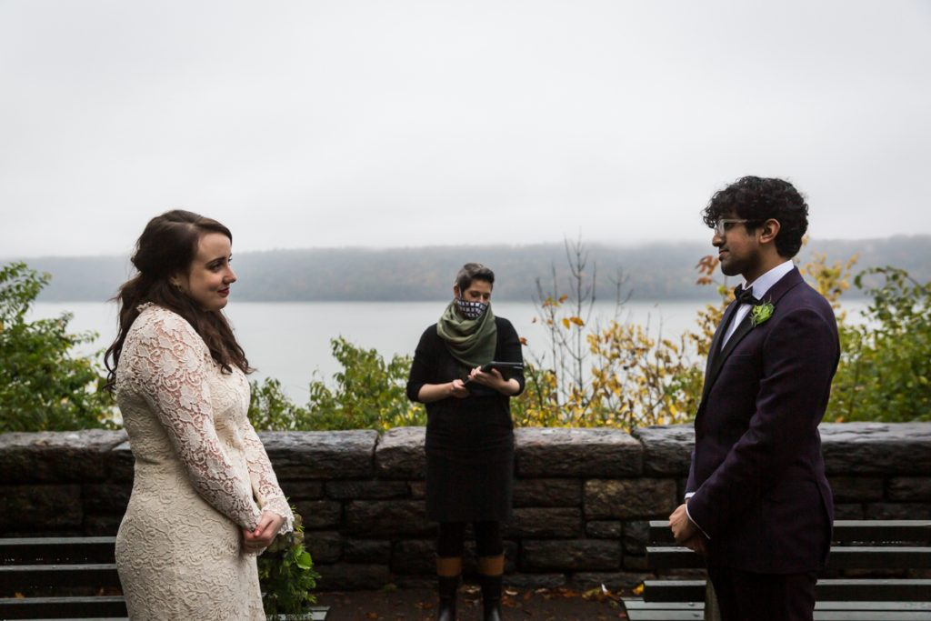 Bride and groom listening to officiant during Fort Tryon Park wedding ceremony