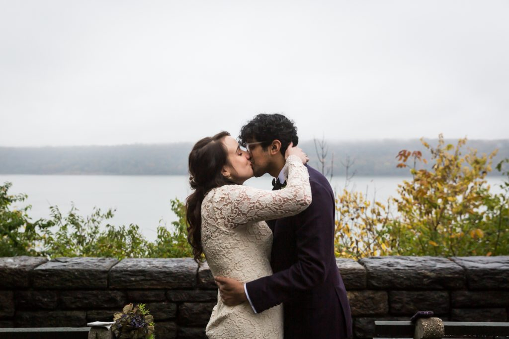 Couple kissing with Hudson River view for an article on how to get married in Fort Tryon Park