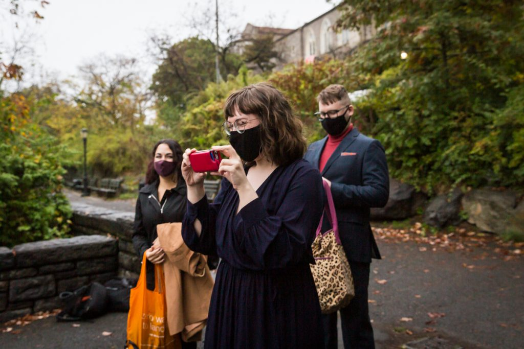Wedding guests wearing masks and taking photos with cell phone at Fort Tryon Park wedding