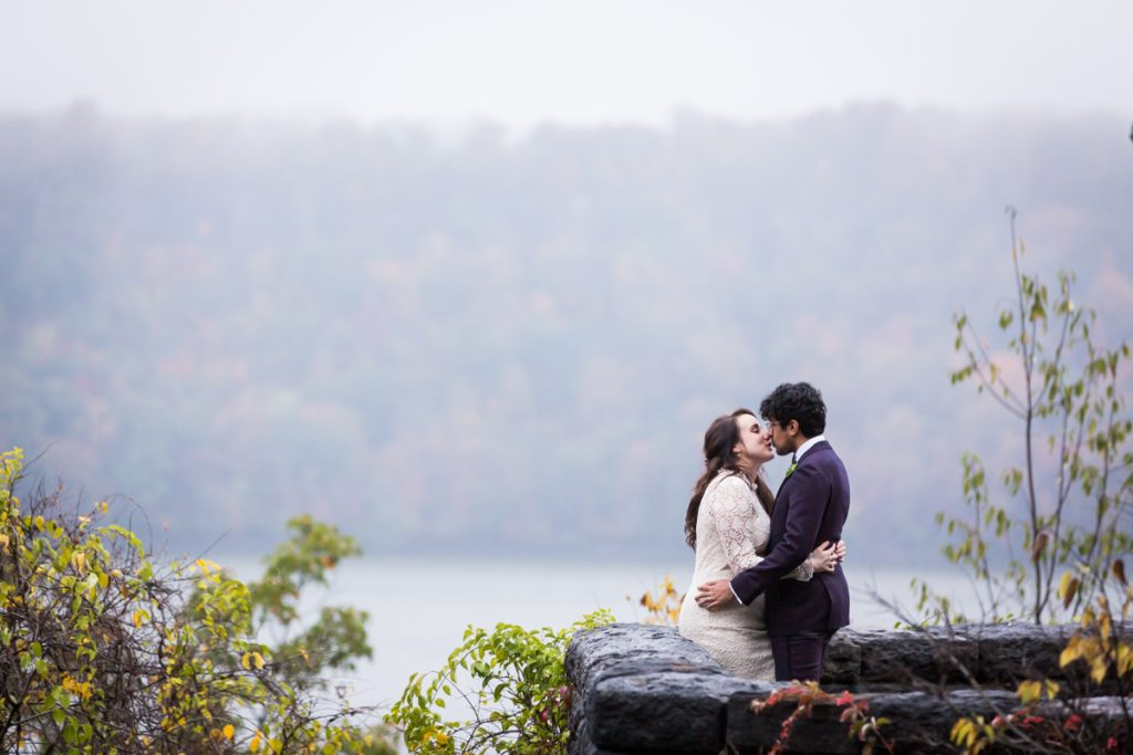 Couple kissing against stone wall for an article on how to get married in Fort Tryon Park