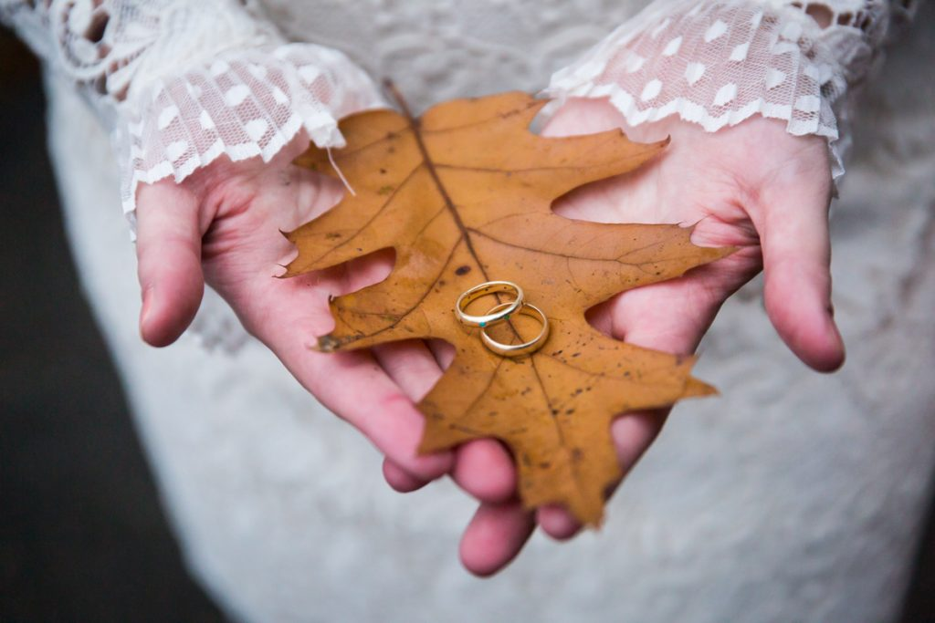 Woman's hands holding brown leaf with wedding rings