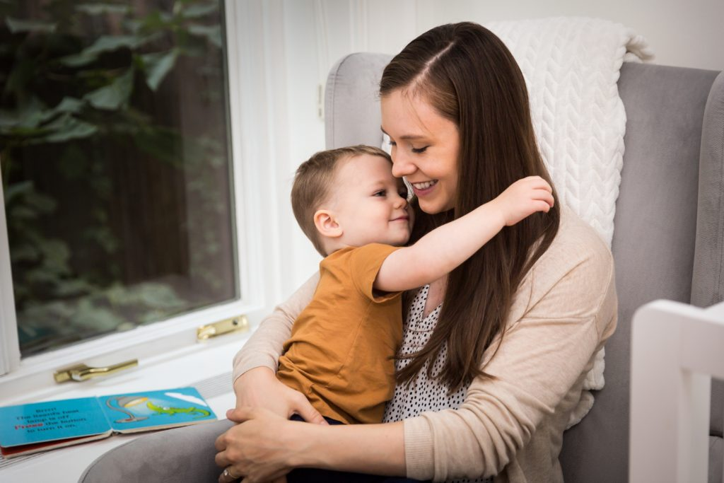 Young son hugging mother for an article on how to prepare for a newborn portrait session