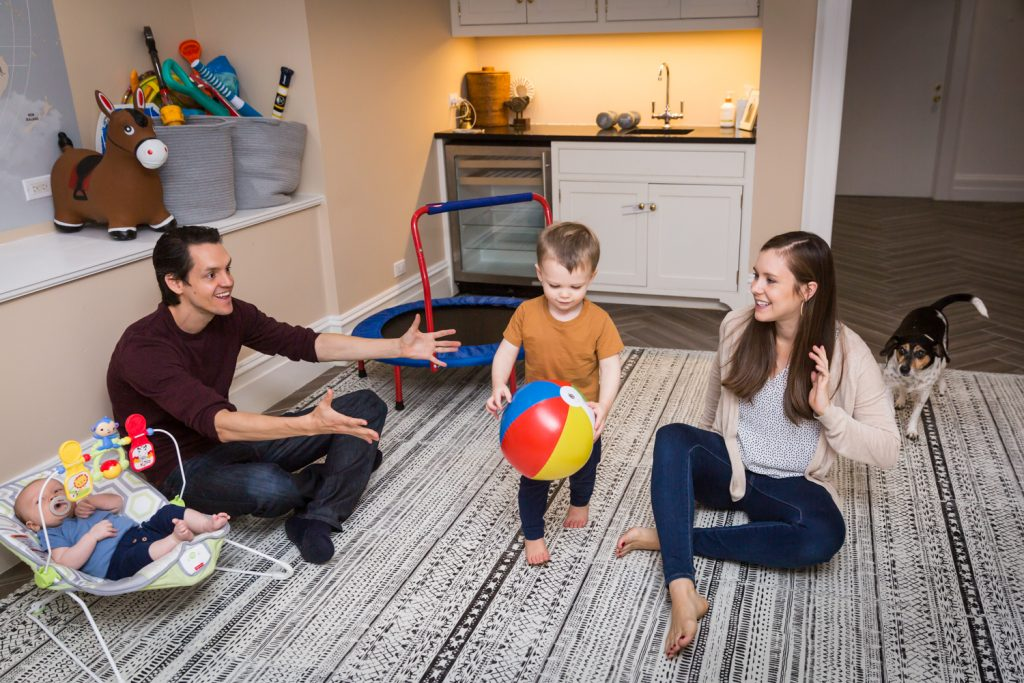 Parents sitting on floor playing with two young sons