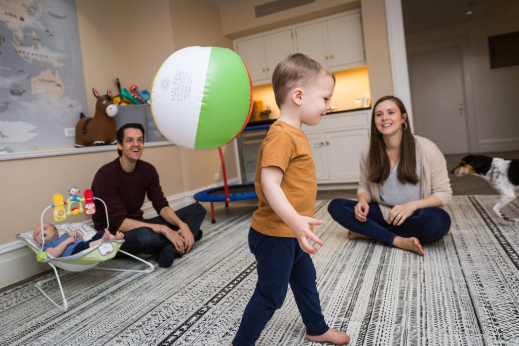 Parents watching young boy and bouncing ball