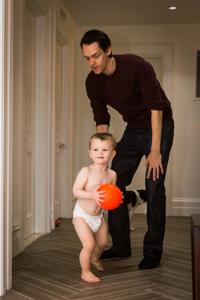 Father chasing after little boy holding red ball