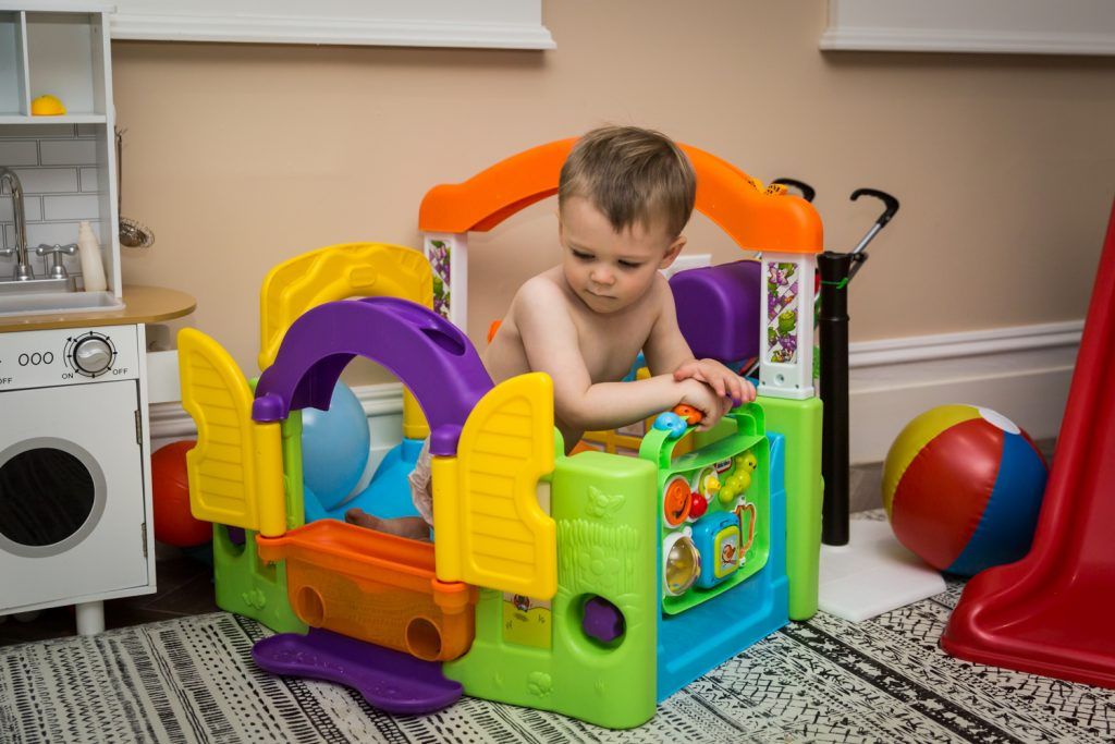 Little boy playing in colorful play castle