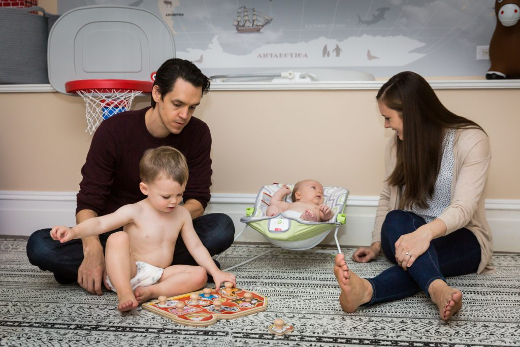 Parents playing on carpet with two young sons for an article on how to prepare for a newborn portrait session