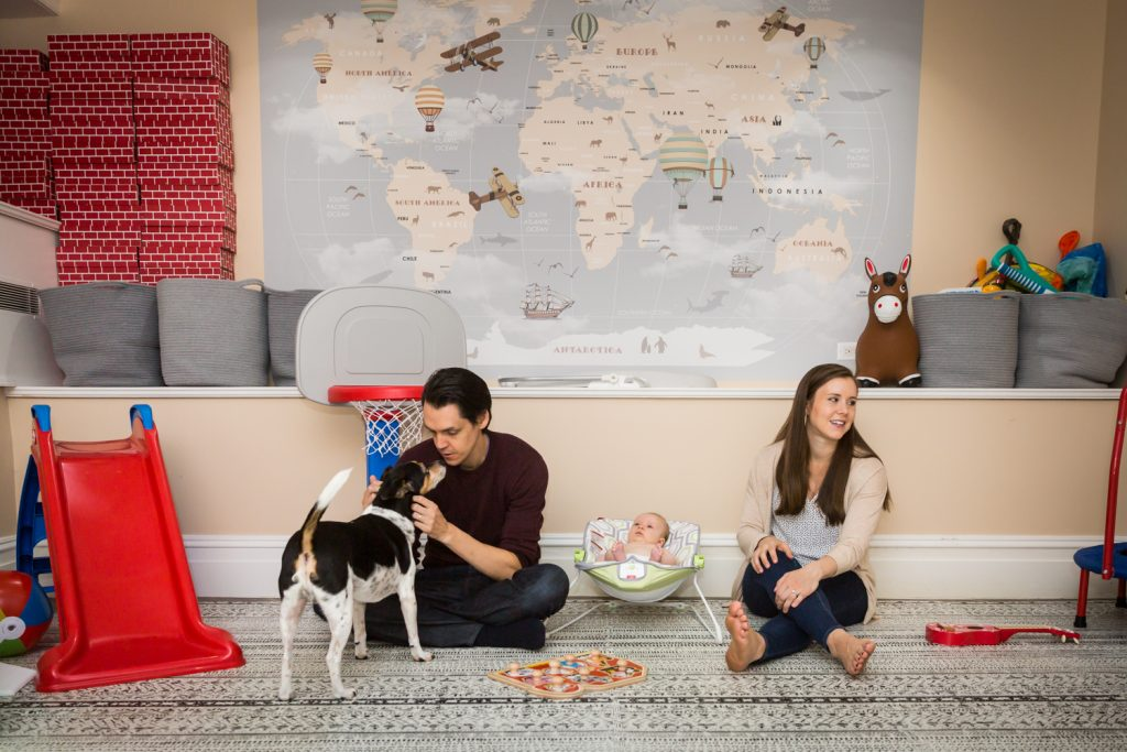 Parents playing with dog and kids on carpet