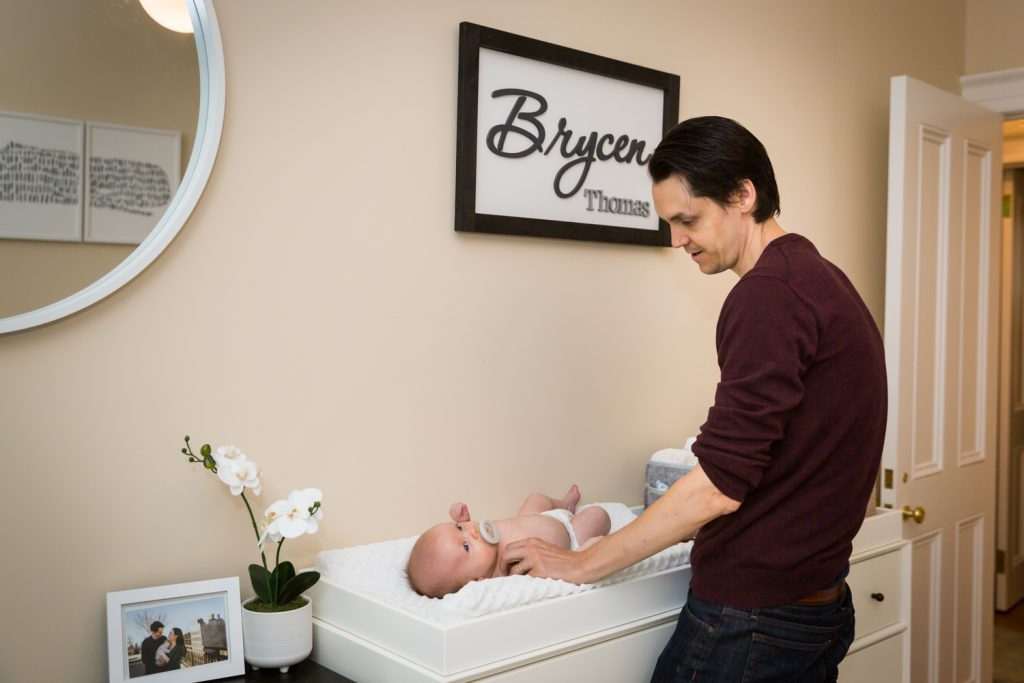 Father changing newborn baby's diaper for an article on how to prepare for a newborn portrait session