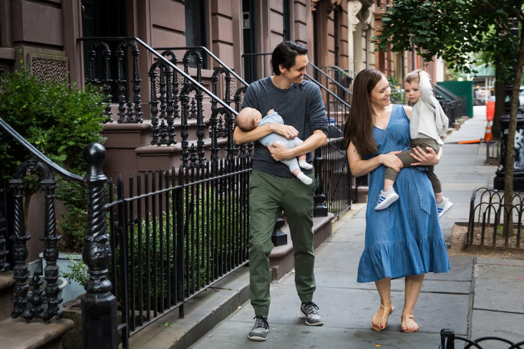 Parents holding two young sons walking down NYC sidewalk for an article on how to prepare for a newborn portrait session