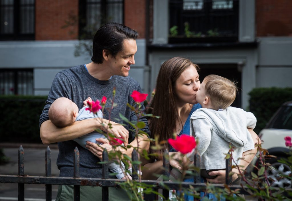 Son kissing mother with father holding newborn for an article on how to prepare for a newborn portrait session