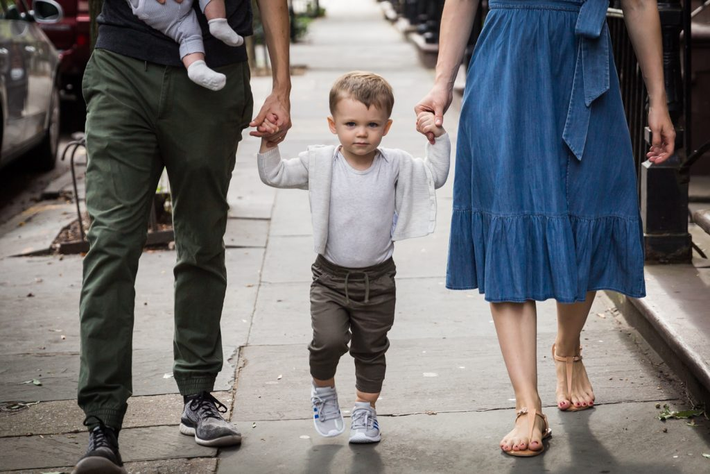 Young boy holding parents' hands on sidewalk