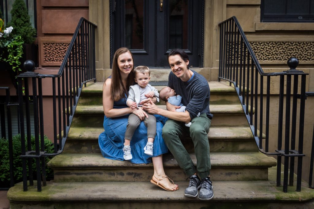 Parents with two young sons sitting on stoop for an article on how to prepare for a newborn portrait session