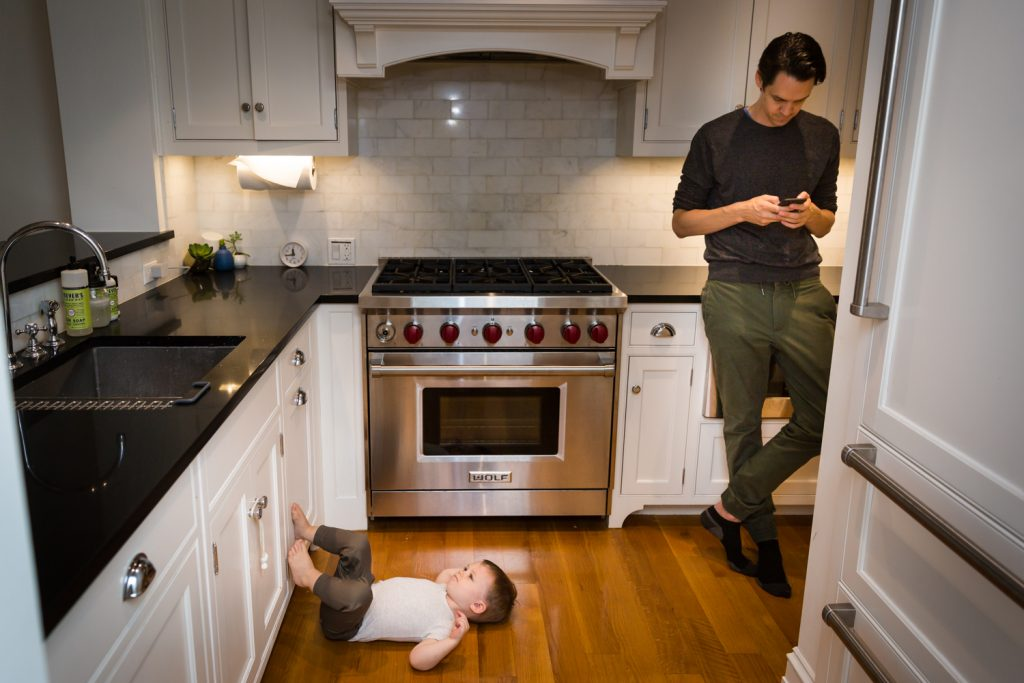 Young toddler with feet on cabinet and father looking at phone for an article on how to prepare for a newborn portrait session