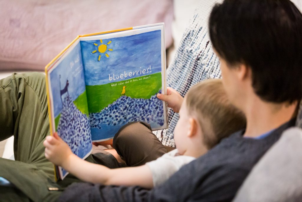 Father and little boy reading book on couch