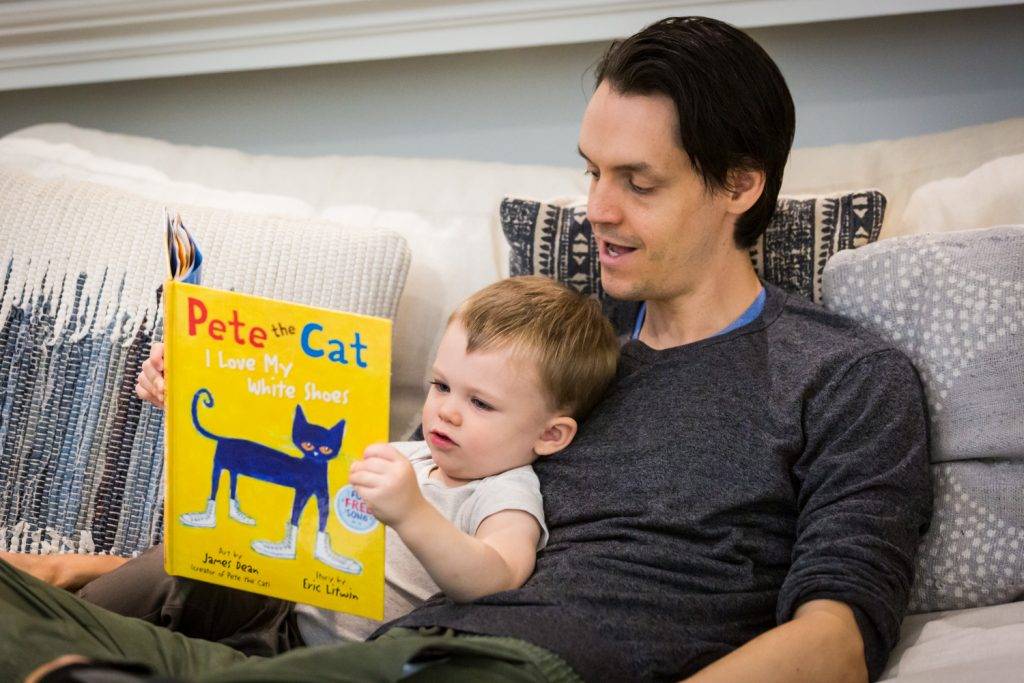 Father and little boy reading yellow book
