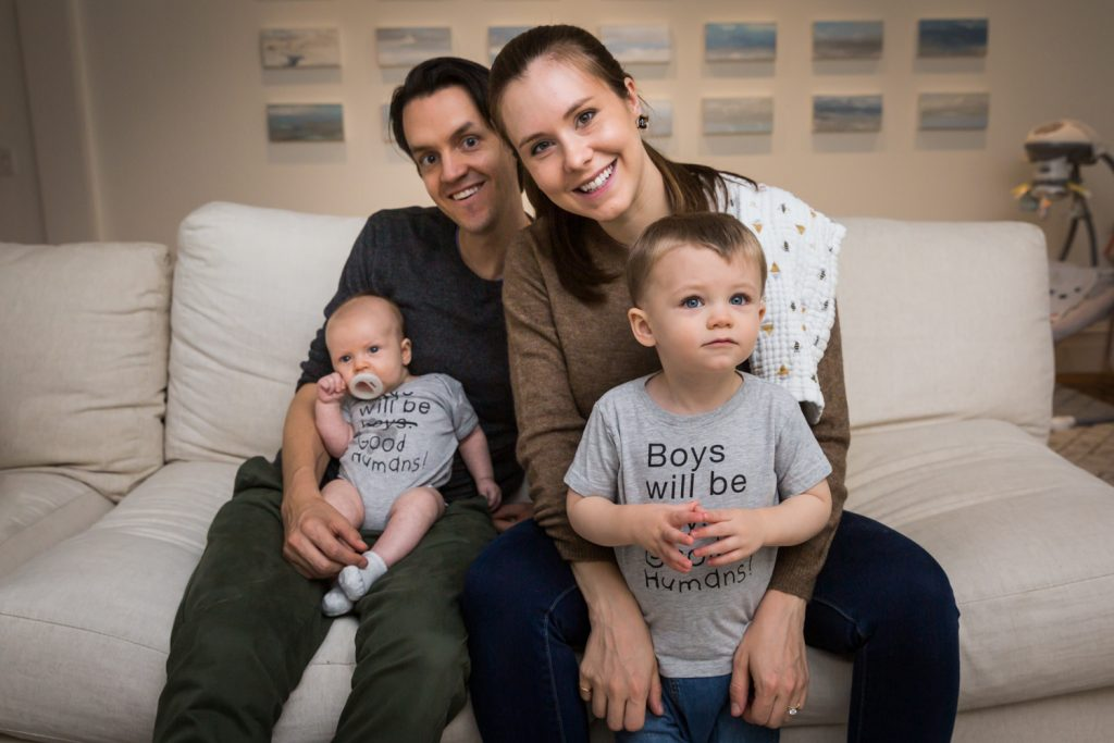 Parents with two young sons on couch for an article on how to prepare for a newborn portrait session