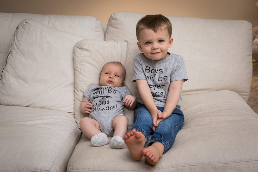 Newborn boy and baby brother on couch for an article on how to prepare for a newborn portrait session