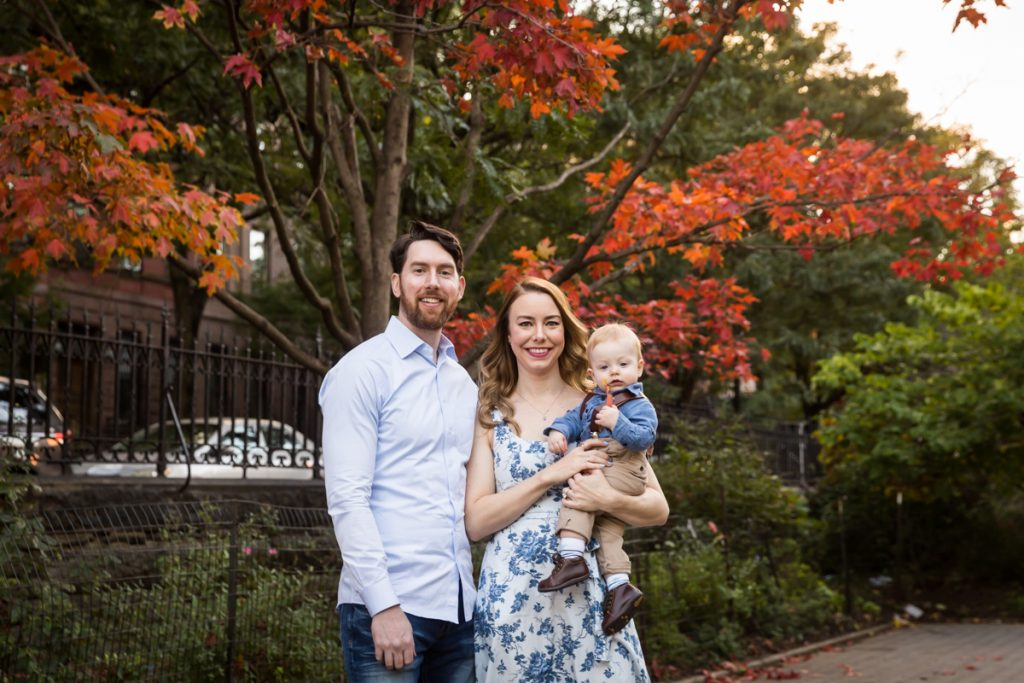 Parents holding baby son in front of tree with red leaves during a Marcus Garvey Park family portrait session