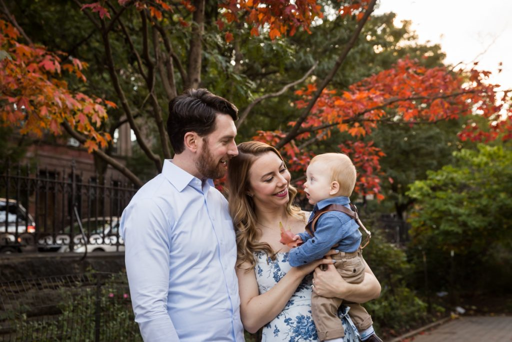 Parents holding baby under tree with red leaves during a Marcus Garvey Park family portrait session