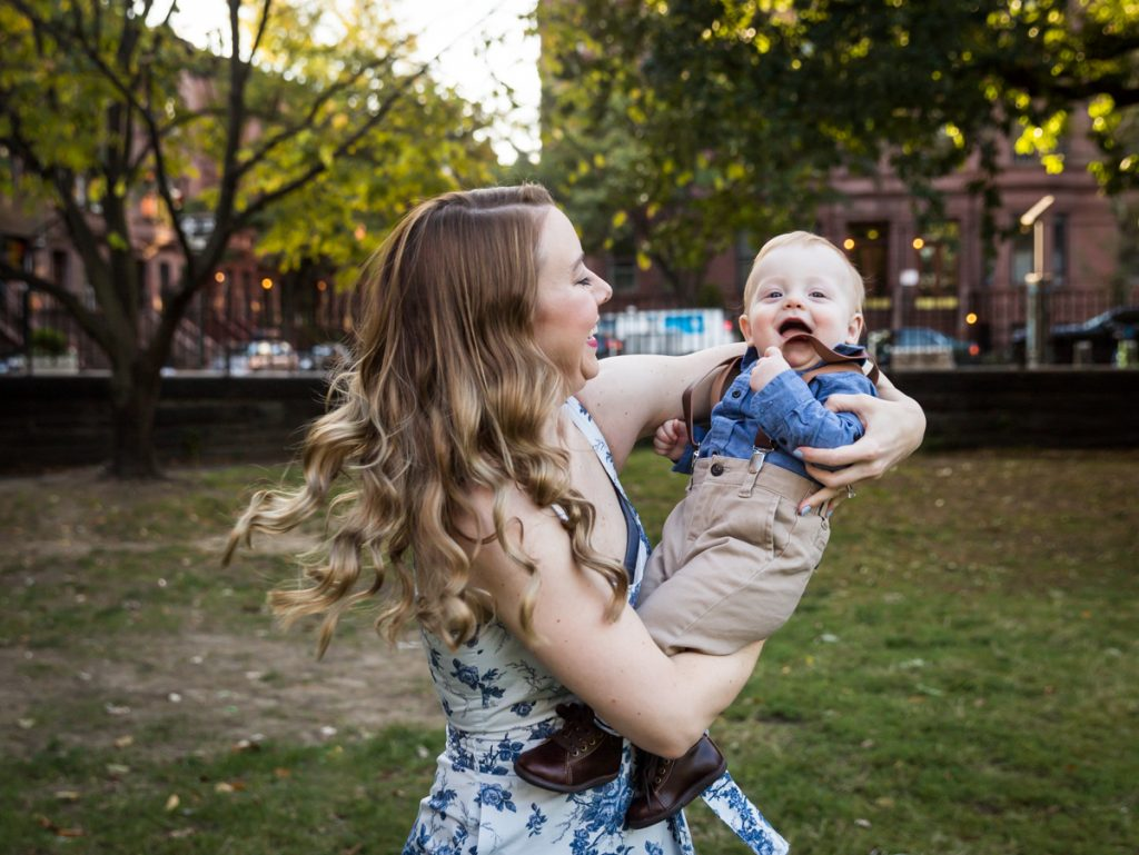 Mother swinging baby son during a Marcus Garvey Park family portrait session