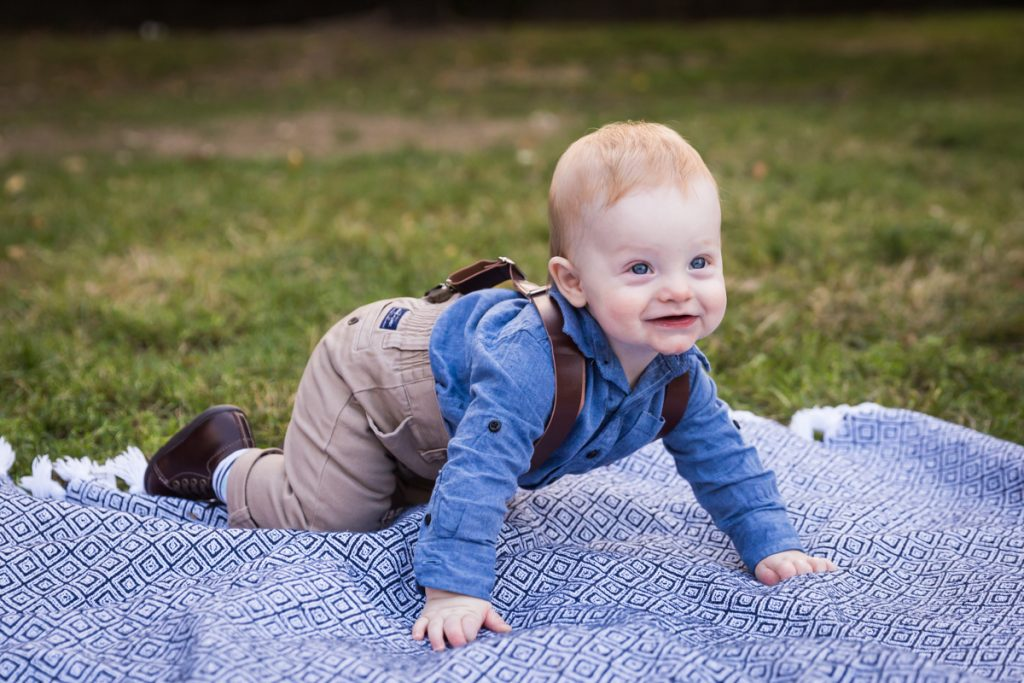 Baby boy crawling on blue blanket in Marcus Garvey Park