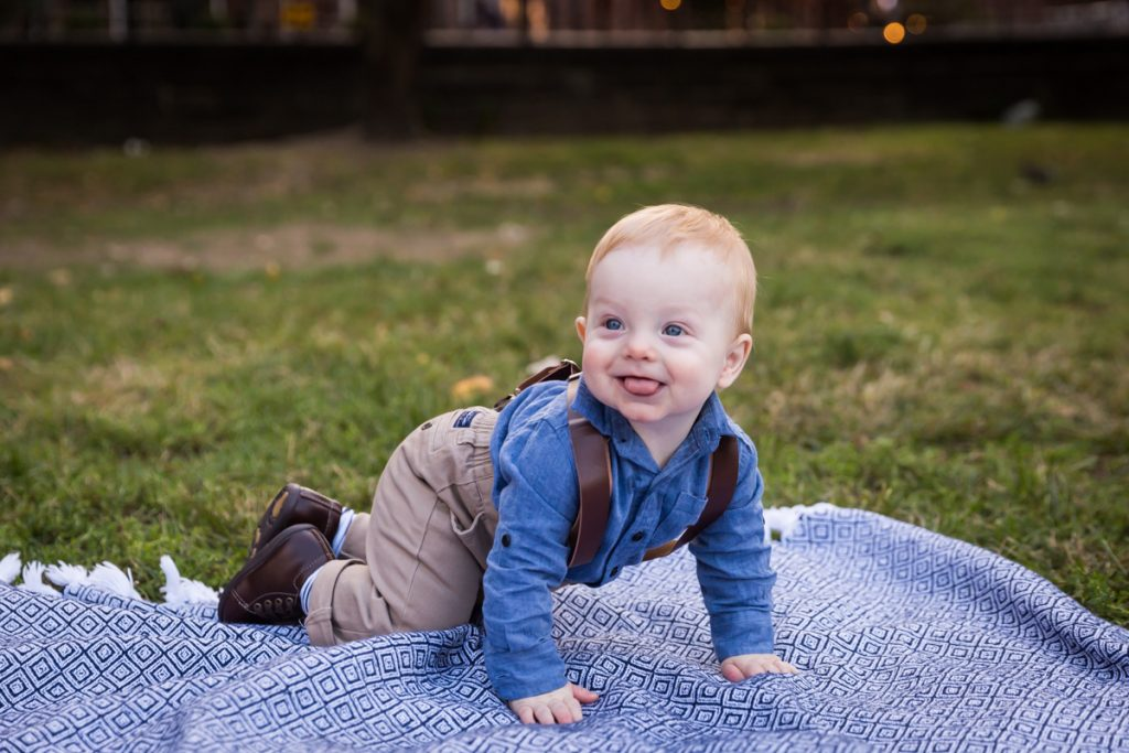 Baby boy wearing suspenders and crawling on blue blanket in Marcus Garvey Park