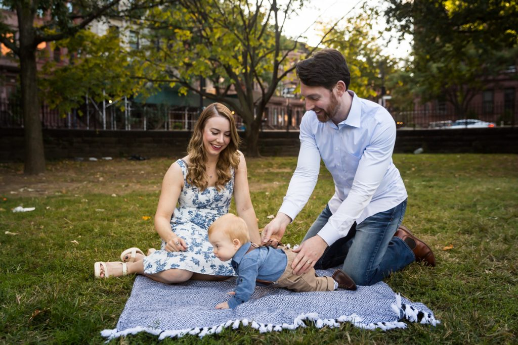 Parents with baby boy on blue blanket in Marcus Garvey Park