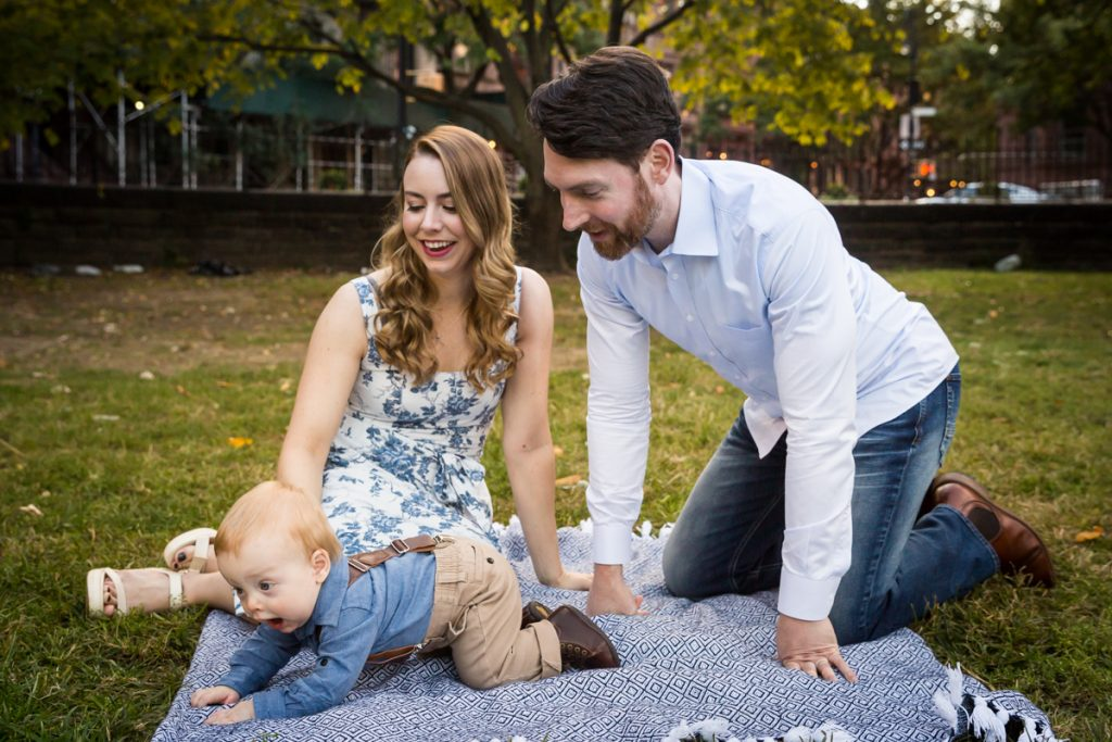 Parents going after baby boy crawling on blue blanket
