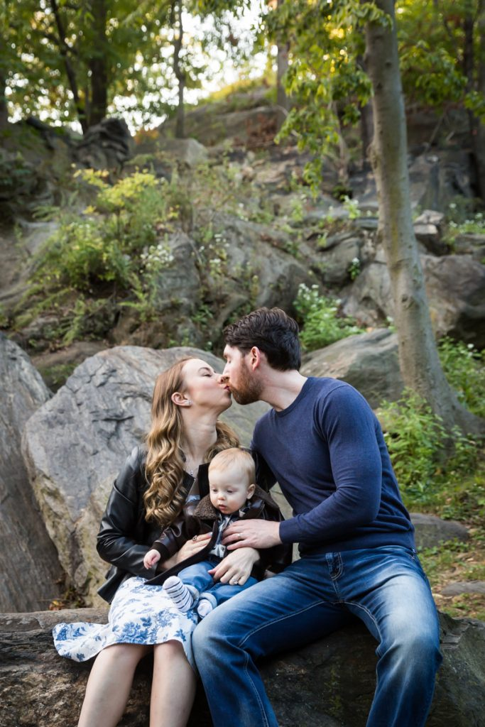 Parents kissing and holding baby boy during a Marcus Garvey Park family portrait session