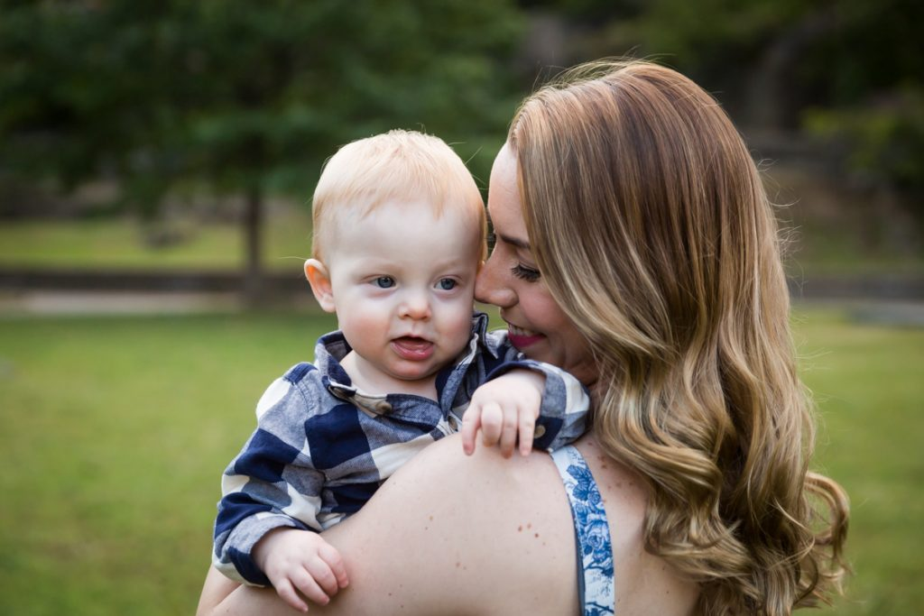 Mother snuggling with baby son over her shoulder during a Marcus Garvey Park family portrait session