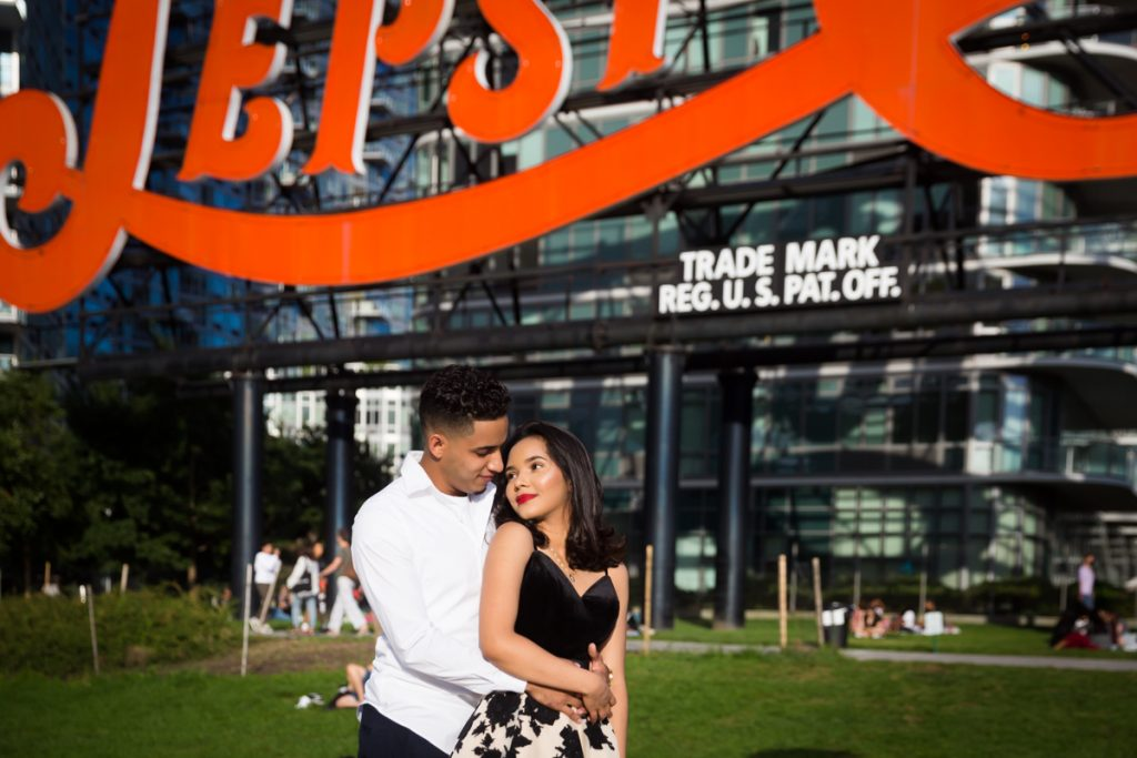 Couple hugging in front of Pepsi Cola neon sign in Gantry Plaza State Park