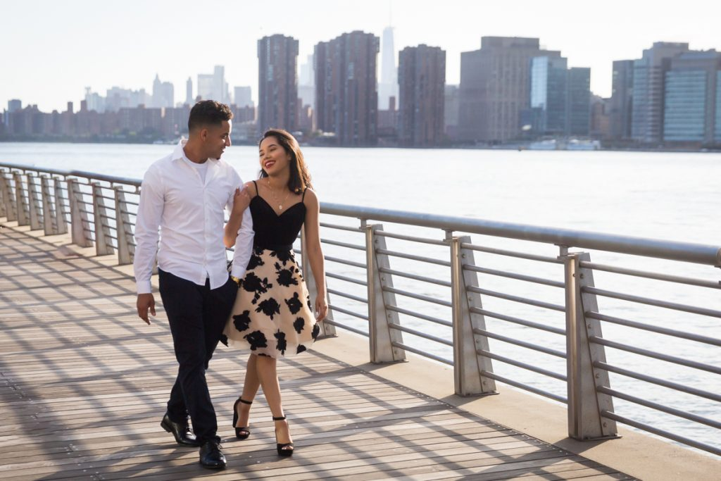 Couple walking along boardwalk at Gantry Plaza State Park for an article on photo shoot details to remember