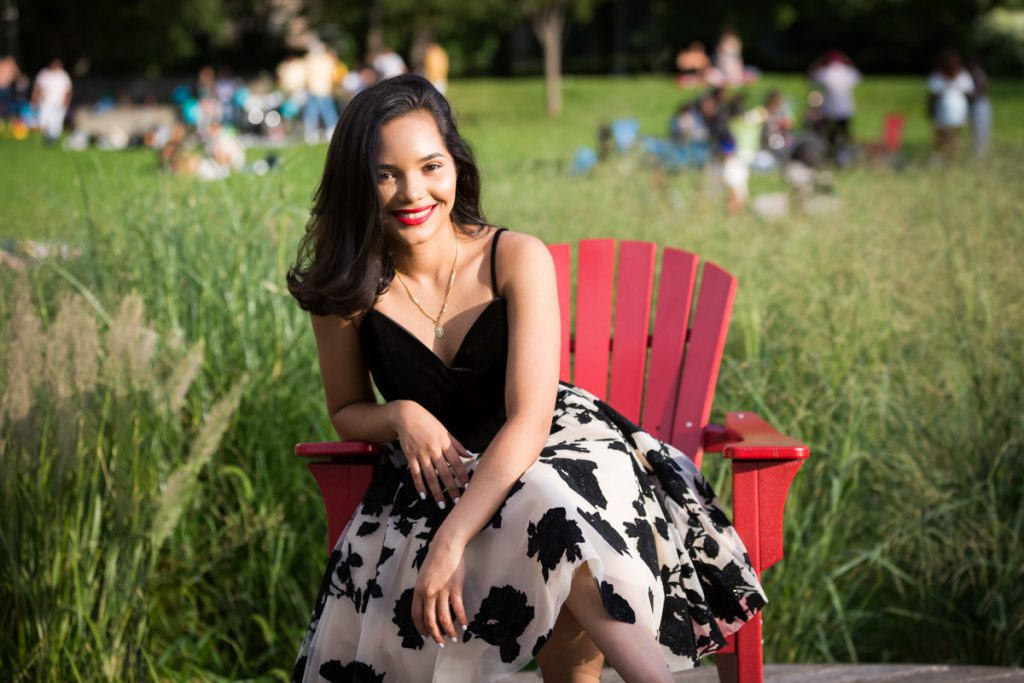 Girl in black and white dress sitting in red chair in Gantry Plaza State Park