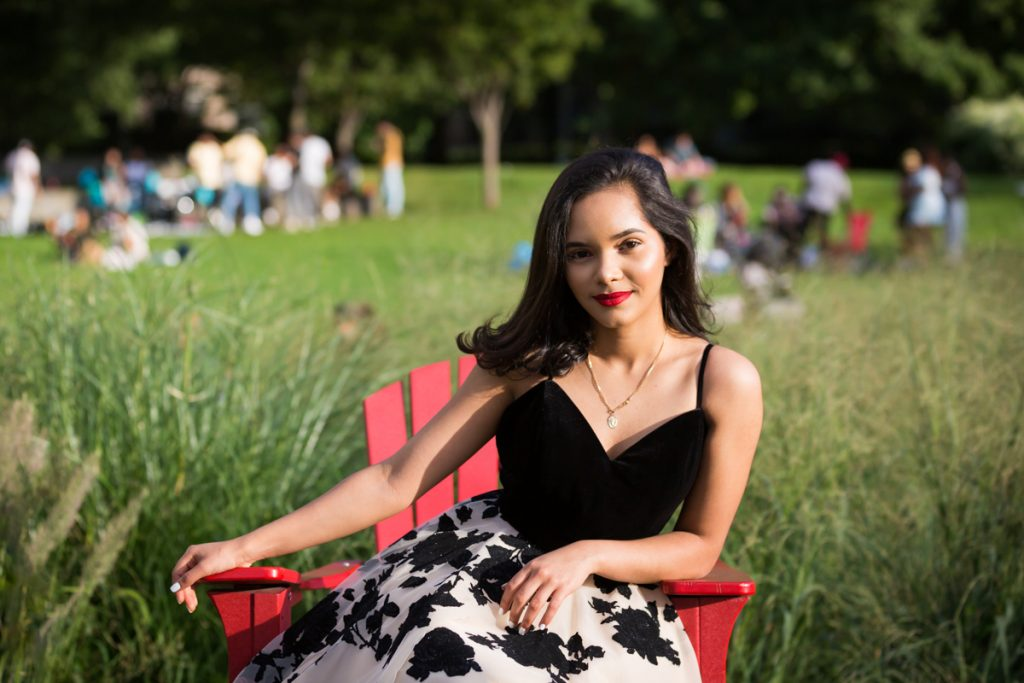 Girl in black and white dress leaning on red chair in Gantry Plaza State Park