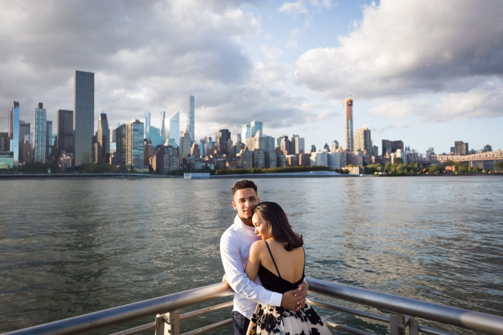 Couple hugging in corner of railing with NYC skyline background