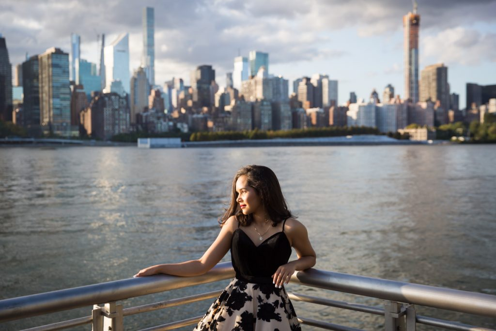 Girl in corner of railing with NYC skyline background