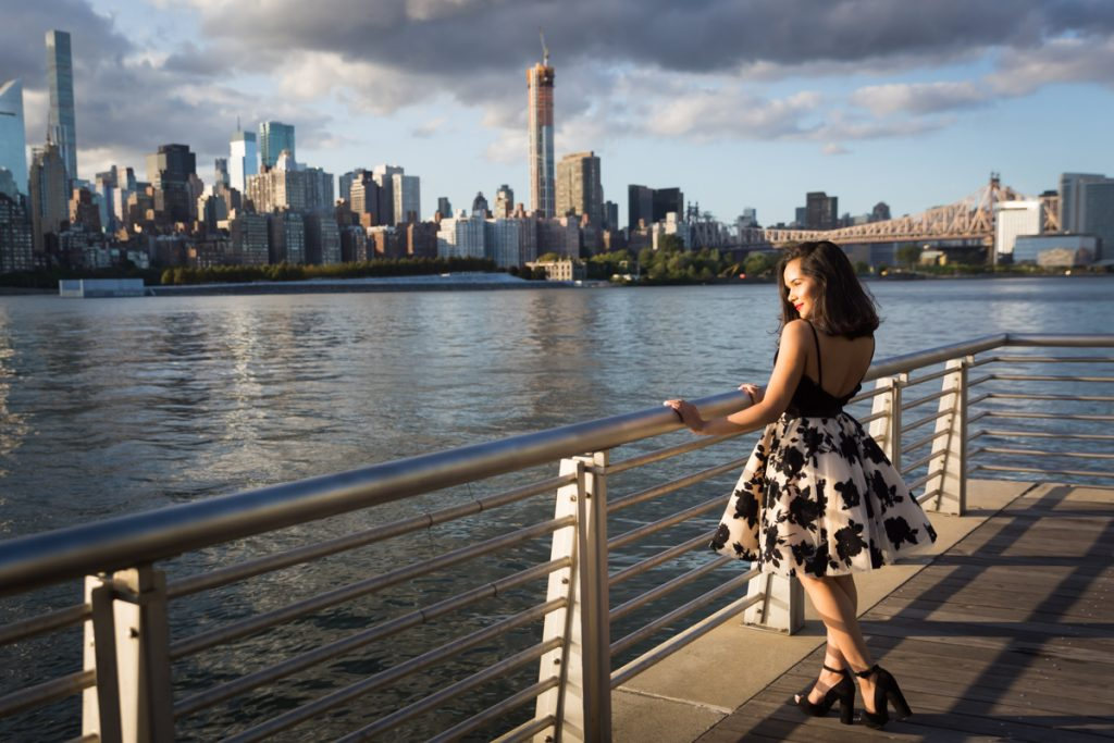 Girl wearing black and white dress holding onto railing for an article on photo shoot details to remember