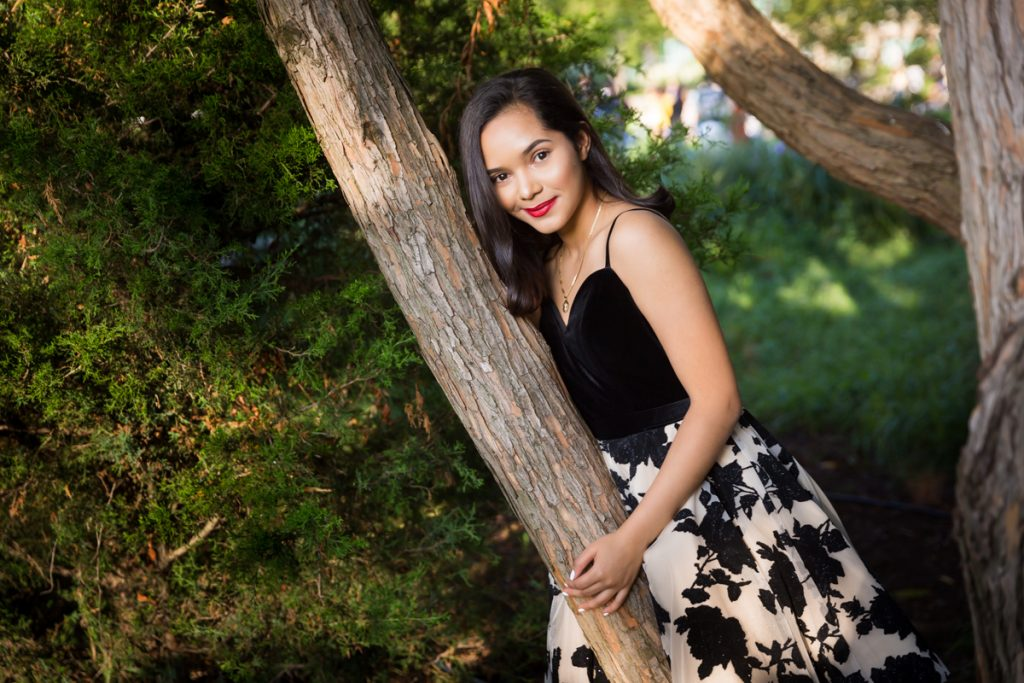 Girl wearing black and white dress leaning against tree for an article on photo shoot details to remember