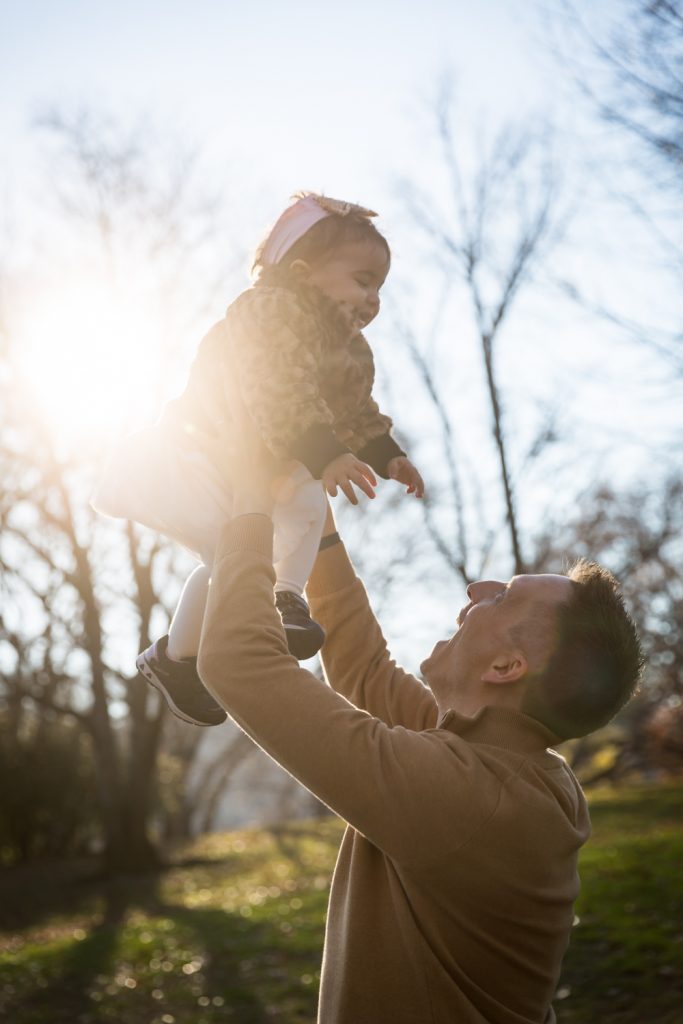 Father lifting little girl in the air for an article on Central Park holiday portrait tips
