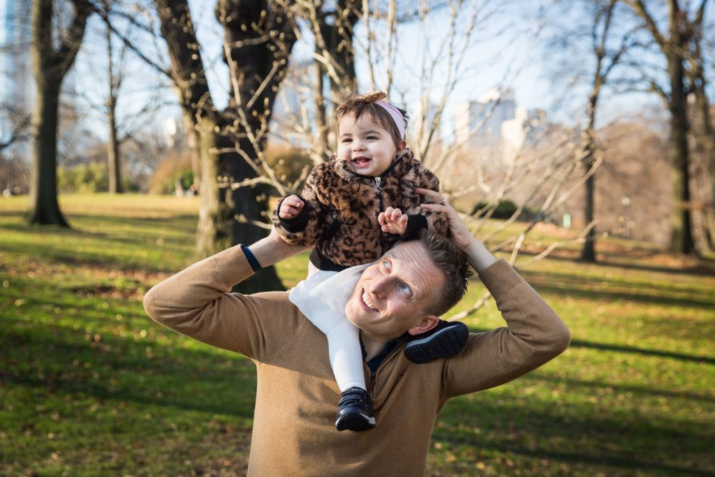 Father playing with little girl on his shoulders in Central Park