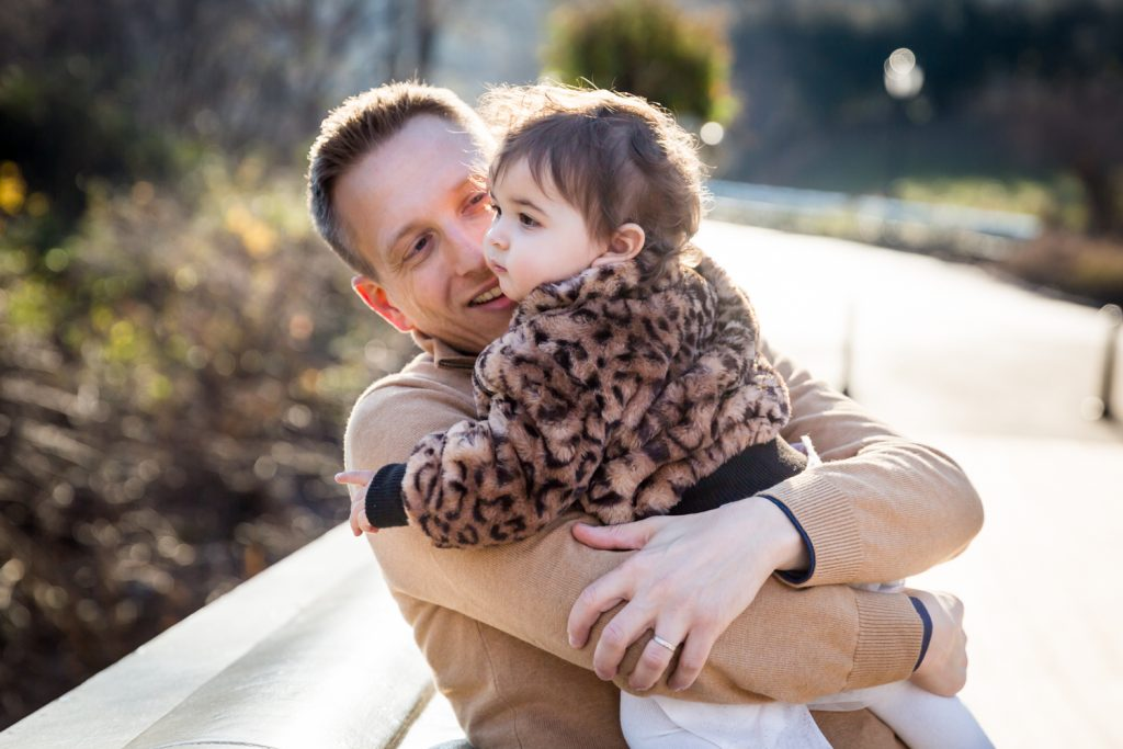 Father holding baby girl on Bow Bridge for an article on Central Park holiday portrait tips