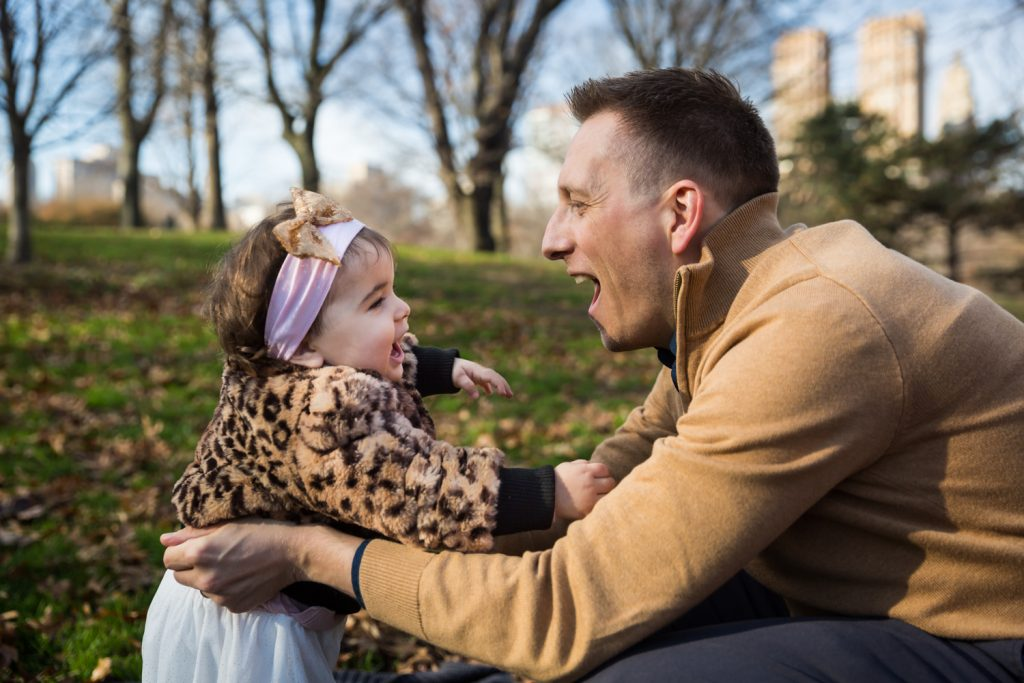 Father playing with little girl in grass in Central Park